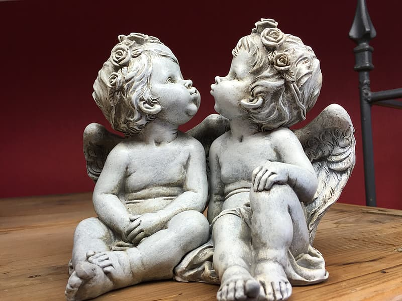 Two cherub kissing each other concrete statuette on wooden surface