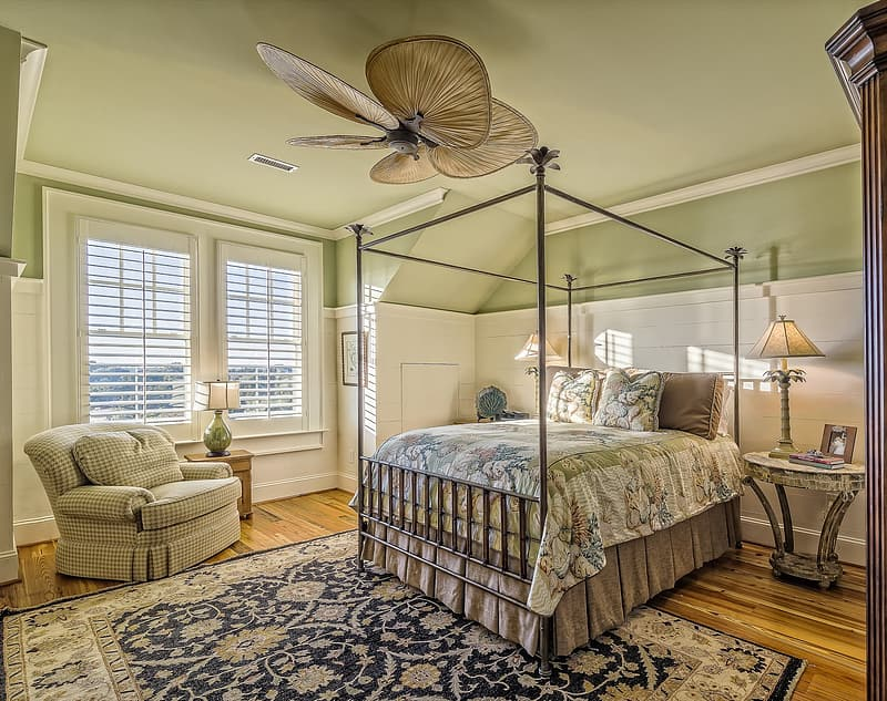 Beige 5-blade ceiling fan under of bedspread