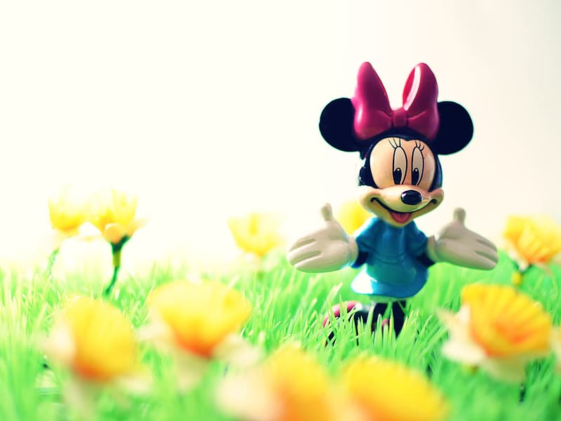 Shallow focus photography of Minnie Mouse figure surrounded by yellow flowers
