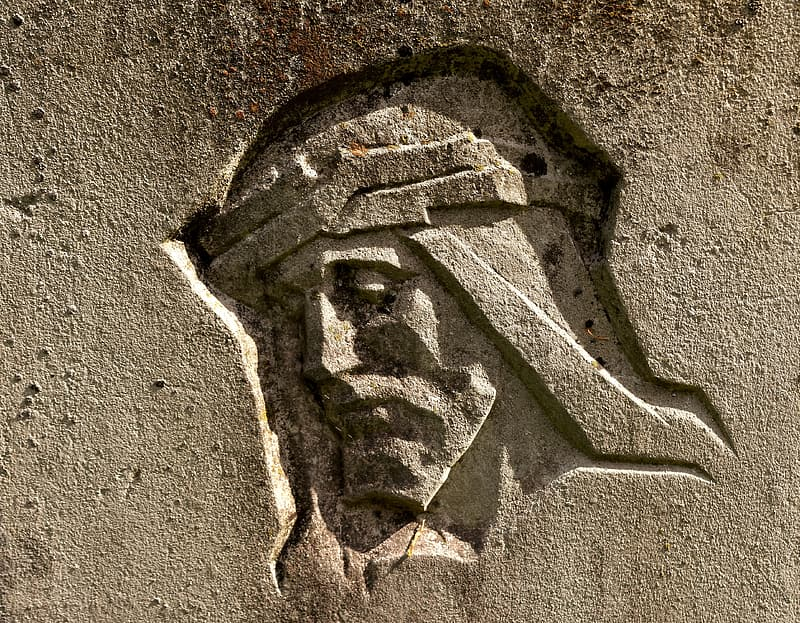 Jesus face carved on brown concrete wall