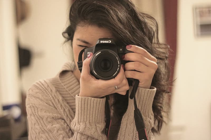 Shallow focus photography of woman in brown sweater using Canon DSLR camera