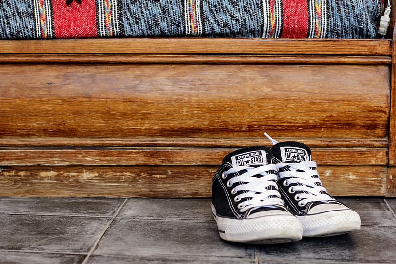 Pair of black-and-white Converse low-top sneakers besides brown wooden panel
