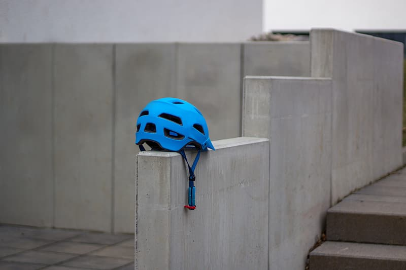 Blue and white bicycle helmet on gray concrete wall