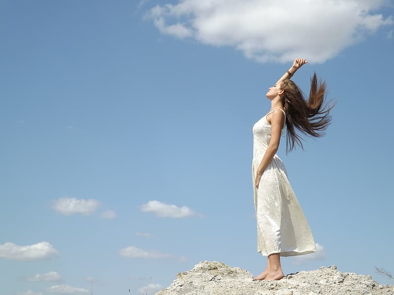 Woman wearing white spaghetti strap dress standing on top of mountain during daytime