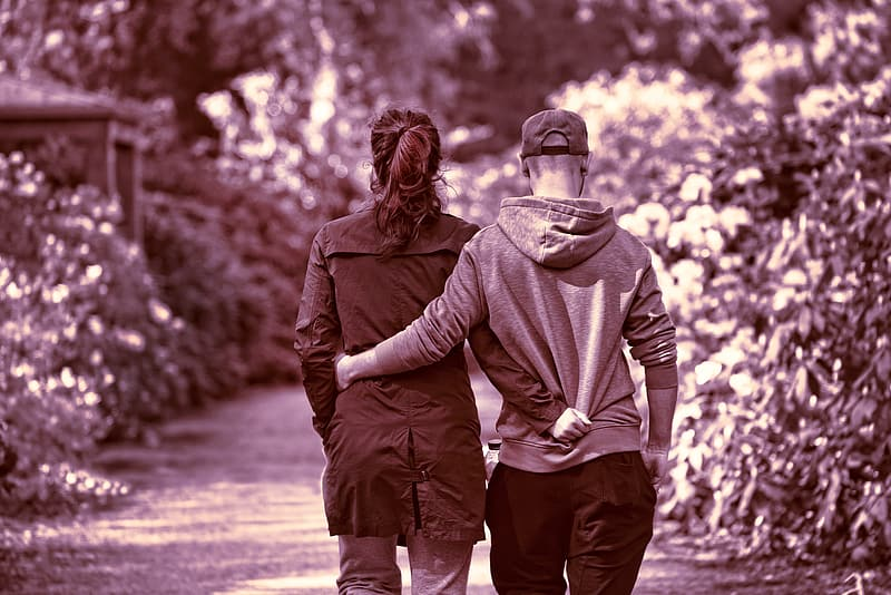 Couple walking on pathway next to plants during daytime