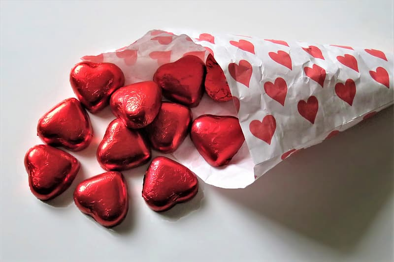 Red heart shaped candies on white paper