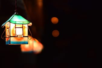 Green and brown lantern with bokeh lights