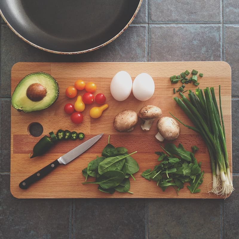Assorted vegetables and pair of eggs on chopping board