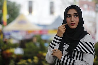 Woman in black hijab and white and black stripe long sleeve shirt