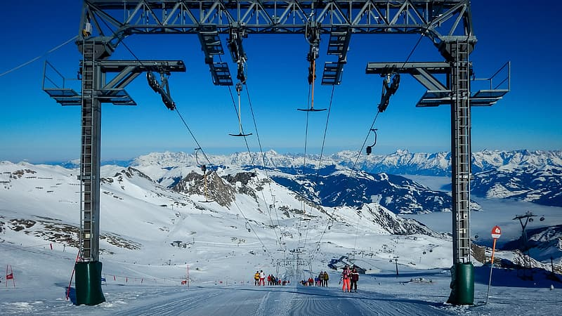 People Riding Ski Lift Over Snow Covered Mountain During