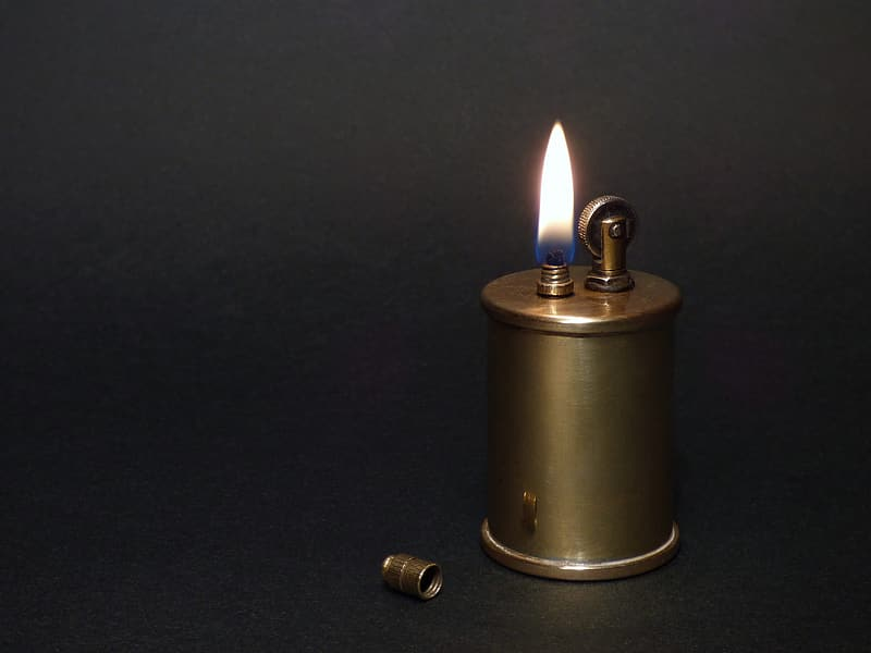 Gold colored pillar candle on black surface