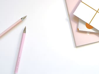 Close-up photo of two pink pencils near papers on white surface