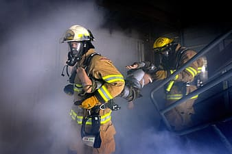 Two firemen carrying a man inside dark room covered with smoke