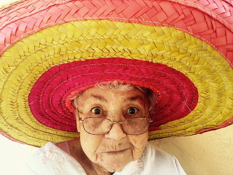 Woman wearing red and yellow straw hat taking selfie