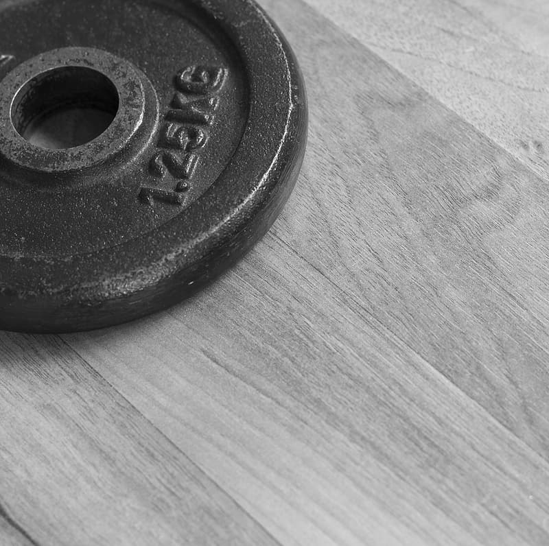 Black dumbbell on brown wooden table