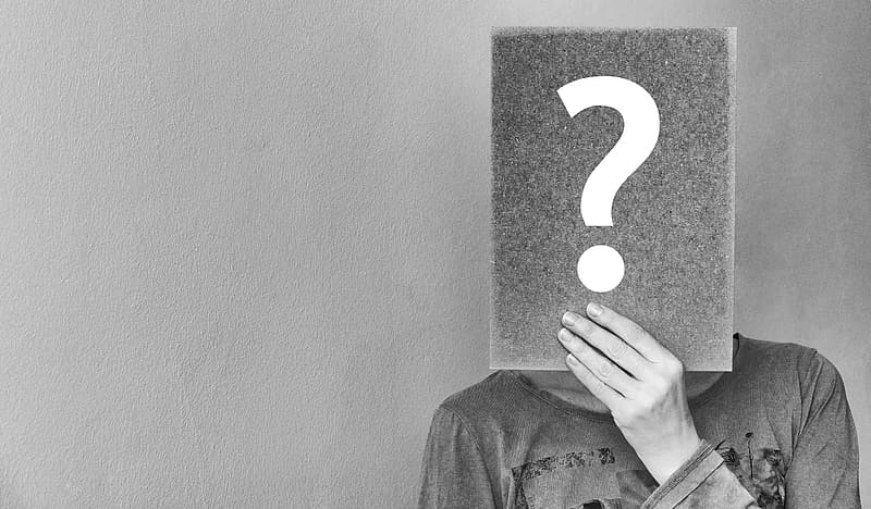 Grayscale picture of a person holding question mark signboard