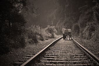 Grayscale photo of three persons walking on railway