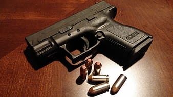 Black semi-automatic pistol with bullets on table