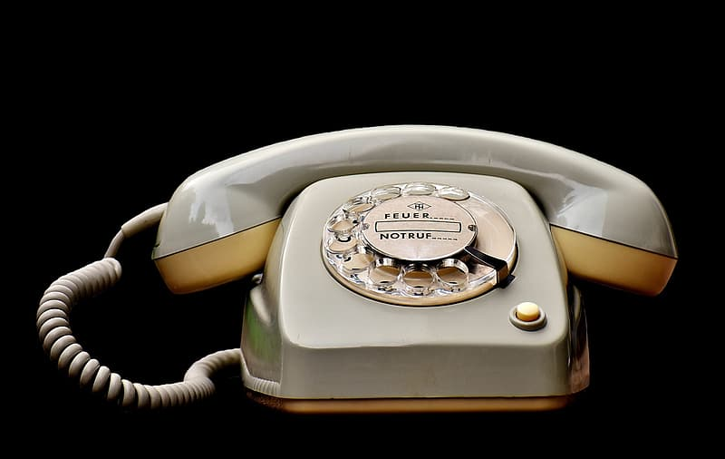 White rotary phone on white surface