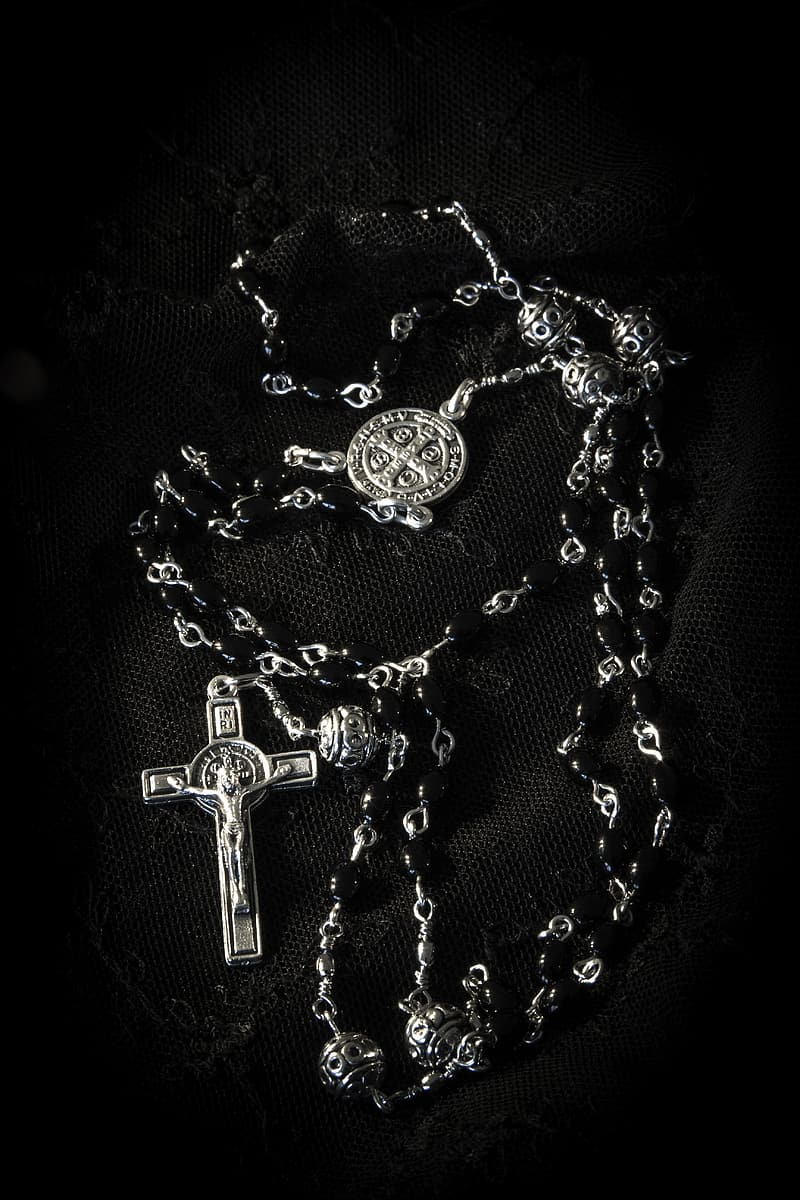 Gray rosary on black surface