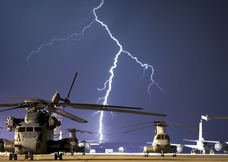 Black helicopters near body of water during lightning