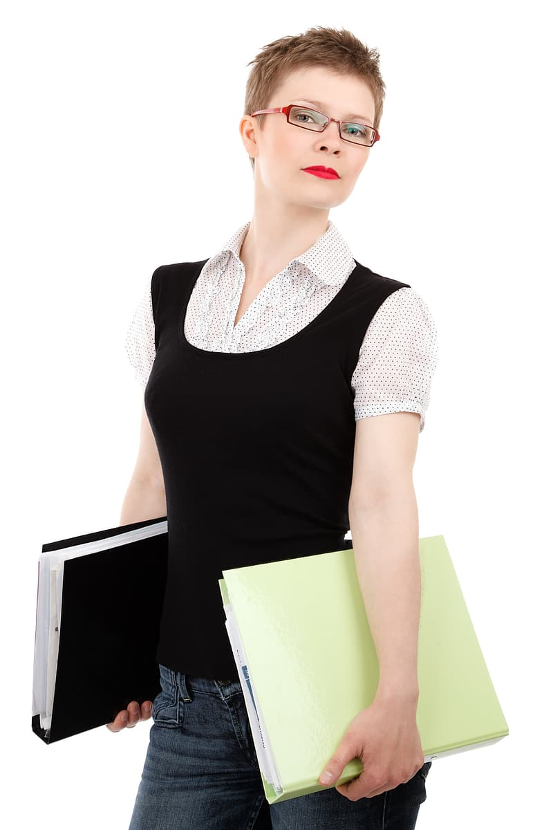 Woman wearing black tank top and white button-up shirt holding green folder