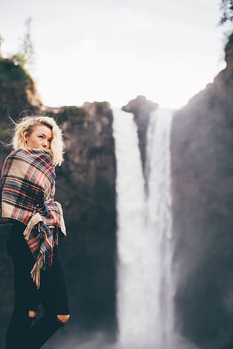 Woman holding brown, red, and blue plaid scarf facing waterfalls