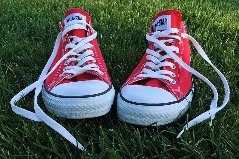 Pair of red-and-white Converse All-Star low on green grassfield