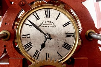 Round gold-colored analog clock on red steel frame