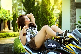 Woman in black shorts and white top lying on black and yellow sports bike during daytime
