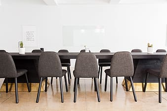 Black armless chairs facing black wooden conference table