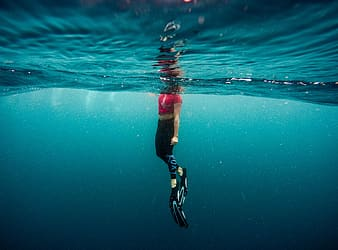 Woman wearing red cap-sleeved top submerge into water