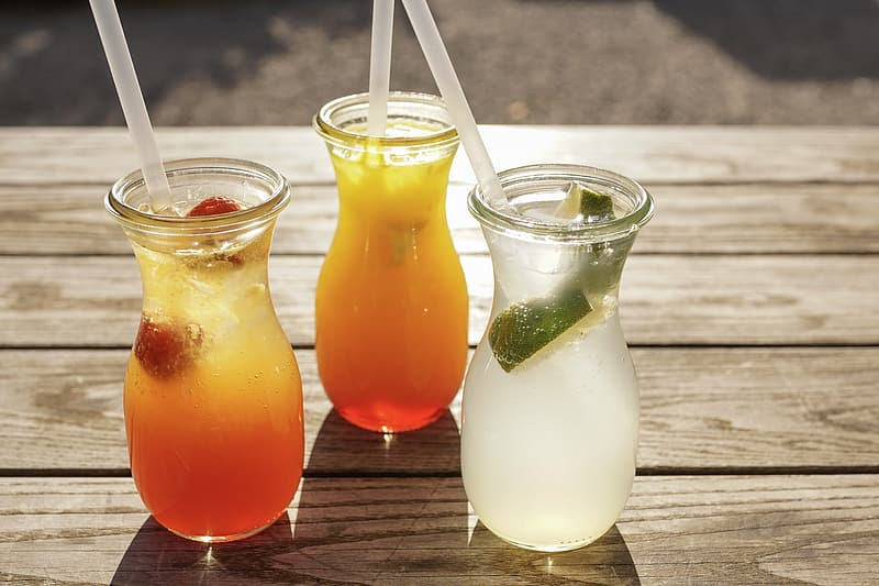 Three clear drinking glasses with orange juice