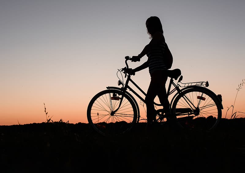 Silhouette of woman holding bicycle