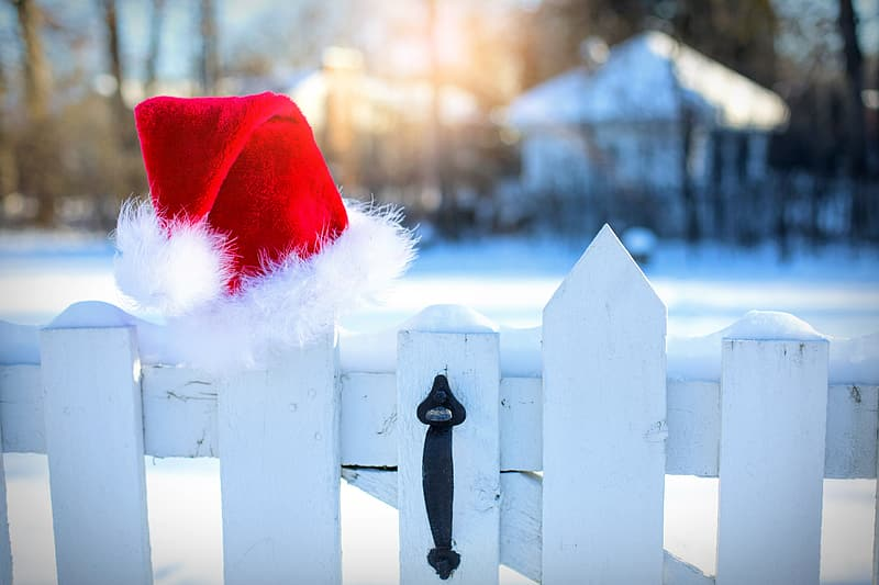 White wooden fence with santa hat on top