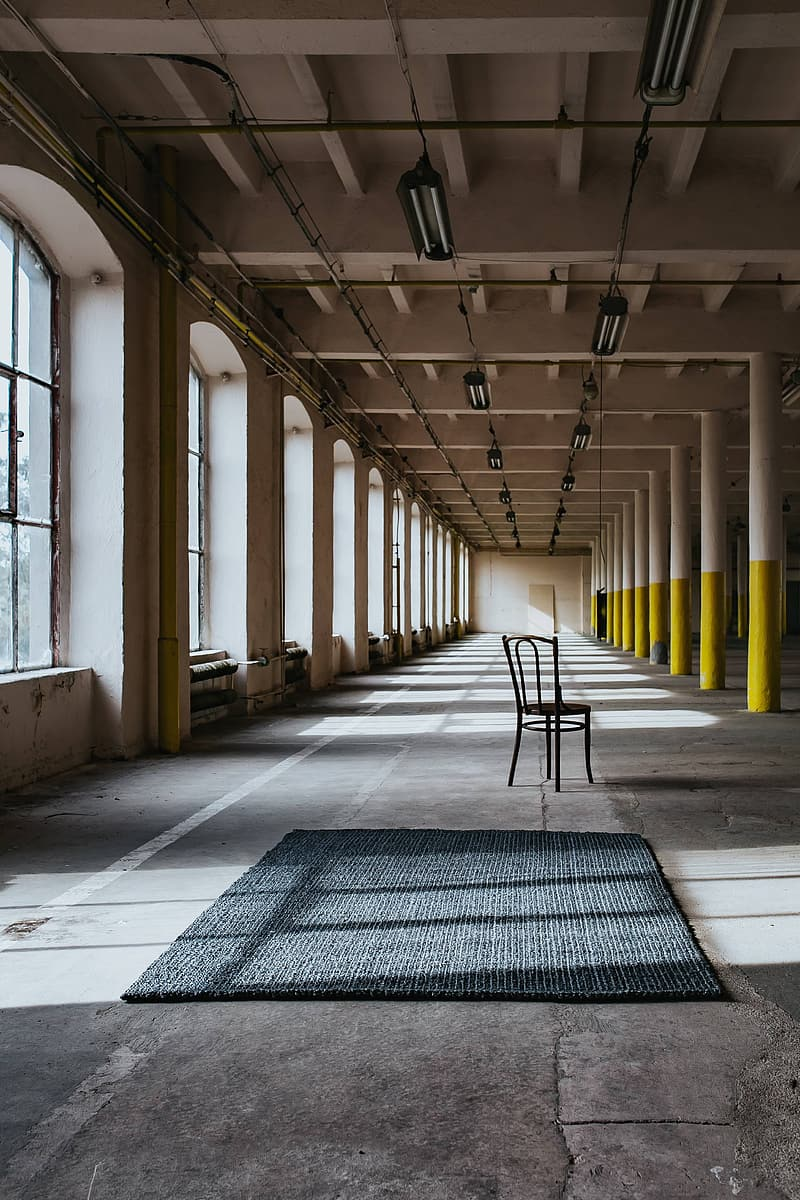 Interior of an abandoned building hall with yellow pillars