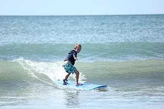 Child surfing on body of water