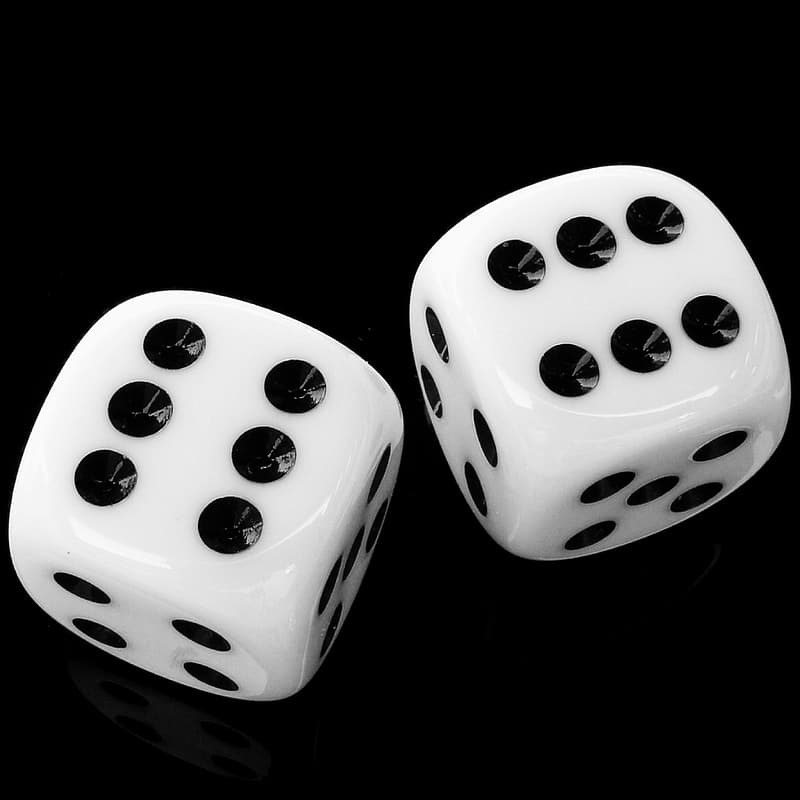 White and black dice on black surface