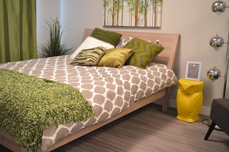 White and brown comforter on brown wooden bed
