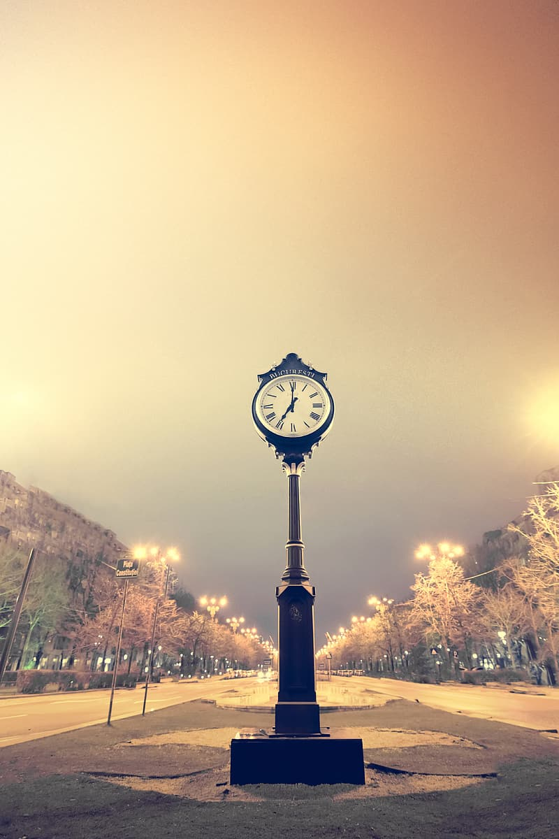Photo of pedestal clock on road at nighttime