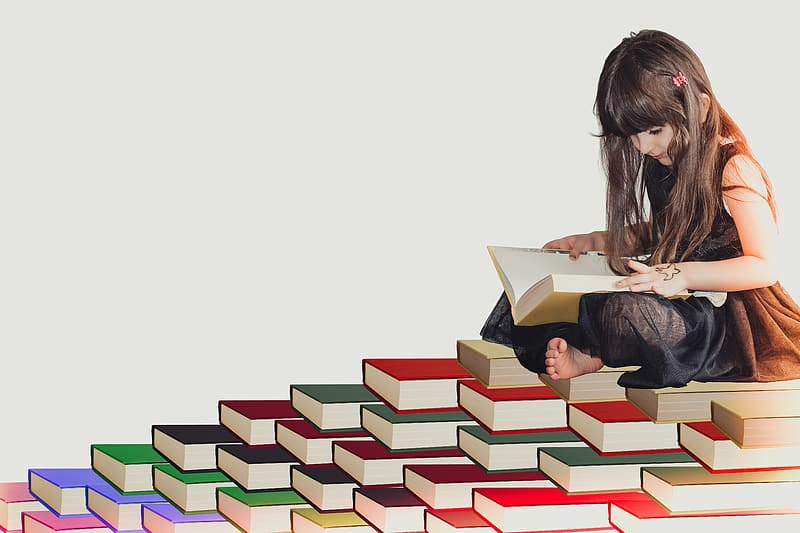 Girl reading book on assorted-color book lot