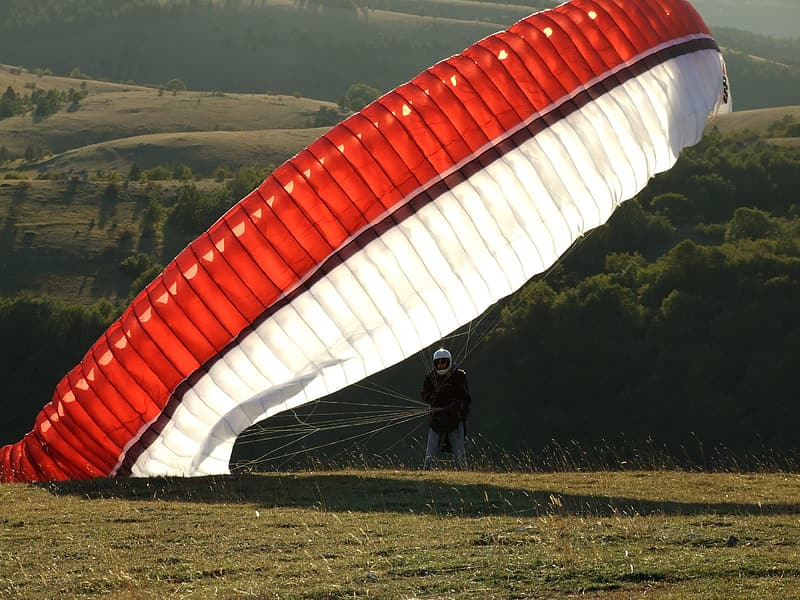 Man in black suit with red parachute