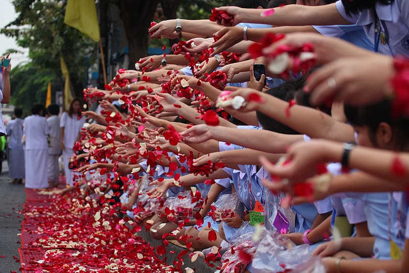 People holding red and white candy sprinkles