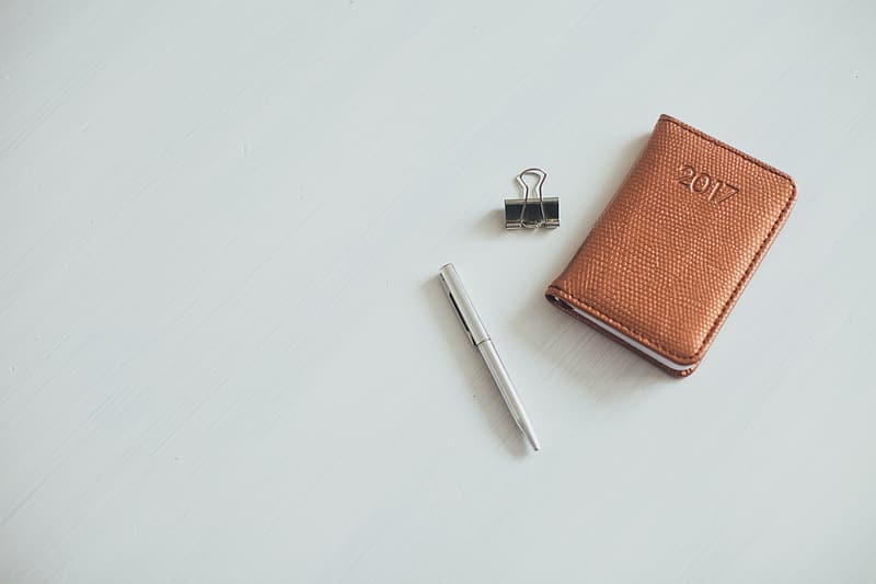 Gray twist pen beside brown leather wallet and paper clip on white surface