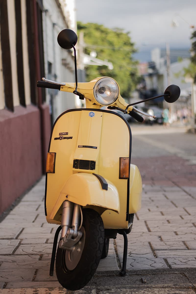 Yellow motor scooter parked on sidewalk during daytime