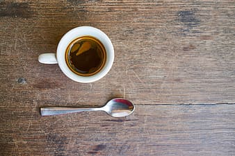 White ceramic teacup and gray spoon on brown wooden surface