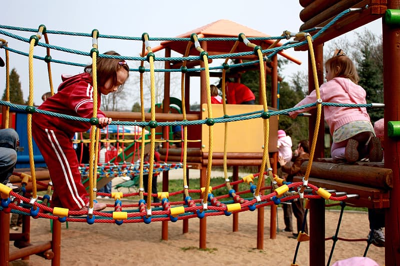Girl in red shirt playing on playground during daytime