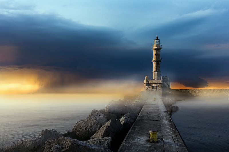 White lighthouse on gray rocky shore during sunset