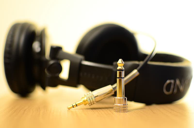 Black corded stereo headphones on wooden surface