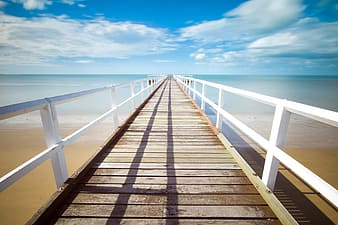 Brown wooden dock under blue sky during daytime